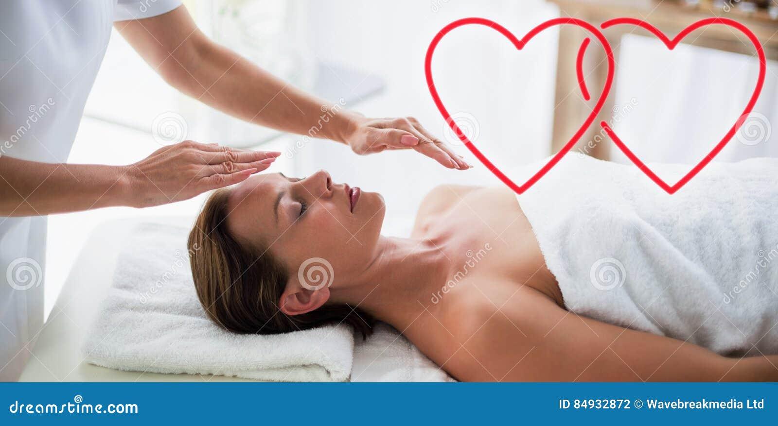 Image composée de reiki de exécution de thérapeute sur des coeurs d amour de femme