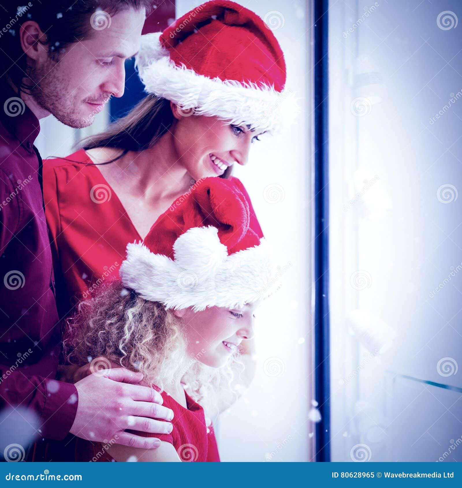 Image composée de vue de côté de famille dans le vêtement de Noël regardant l affichage