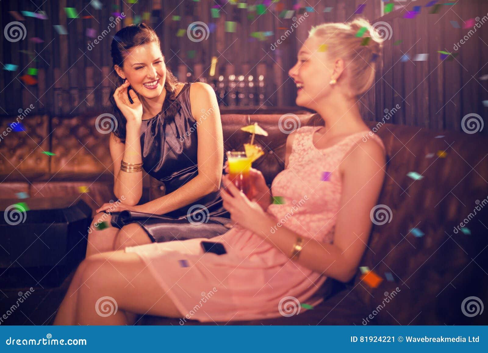 Image composée des amis féminins agissant l un sur l autre les uns avec les autres tout en ayant le cocktail