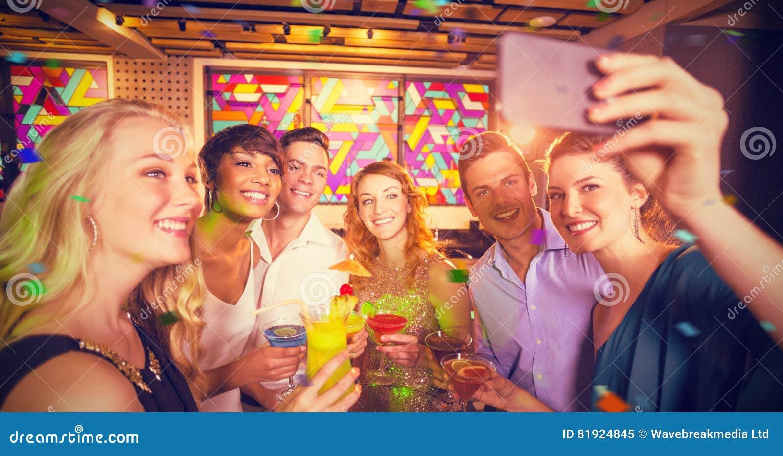 Image composée du groupe d amis prenant le selfie du téléphone portable tout en ayant le cocktail