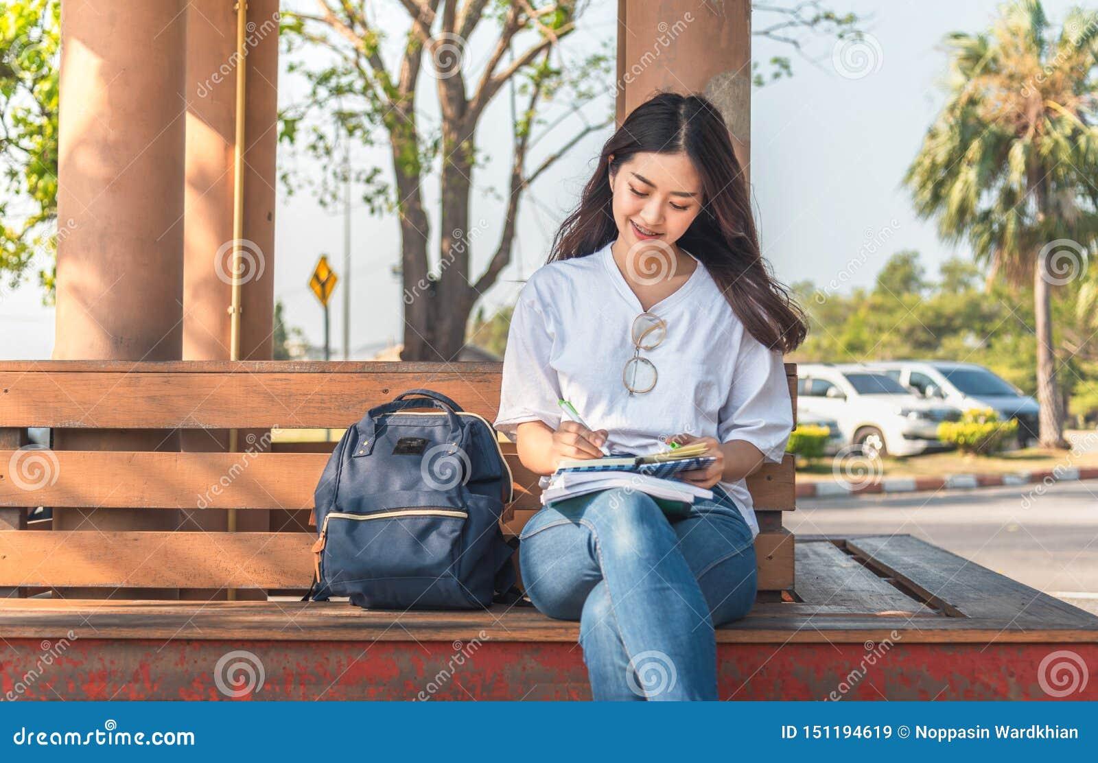 Image d une belle femme étonnante s asseyant sur un banc dans le livre de lecture de parc