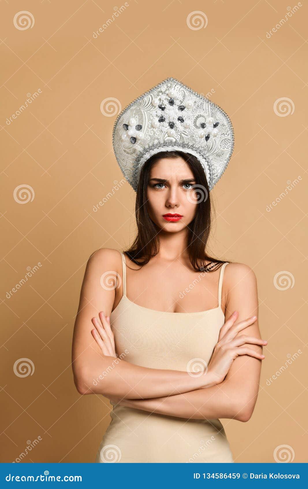 Image de la position fâchée de jeune femme d isolement au-dessus du fond nu regard de l appareil-photo