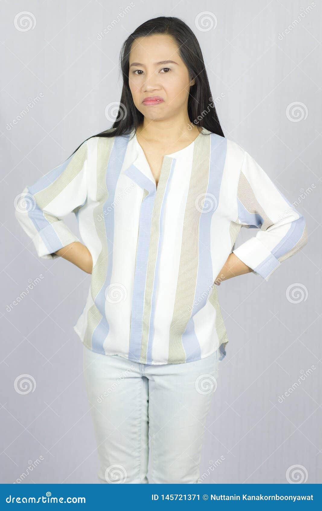 Image de la position f?ch?e de jeune femme d isolement au-dessus du fond gris regard de l appareil-photo