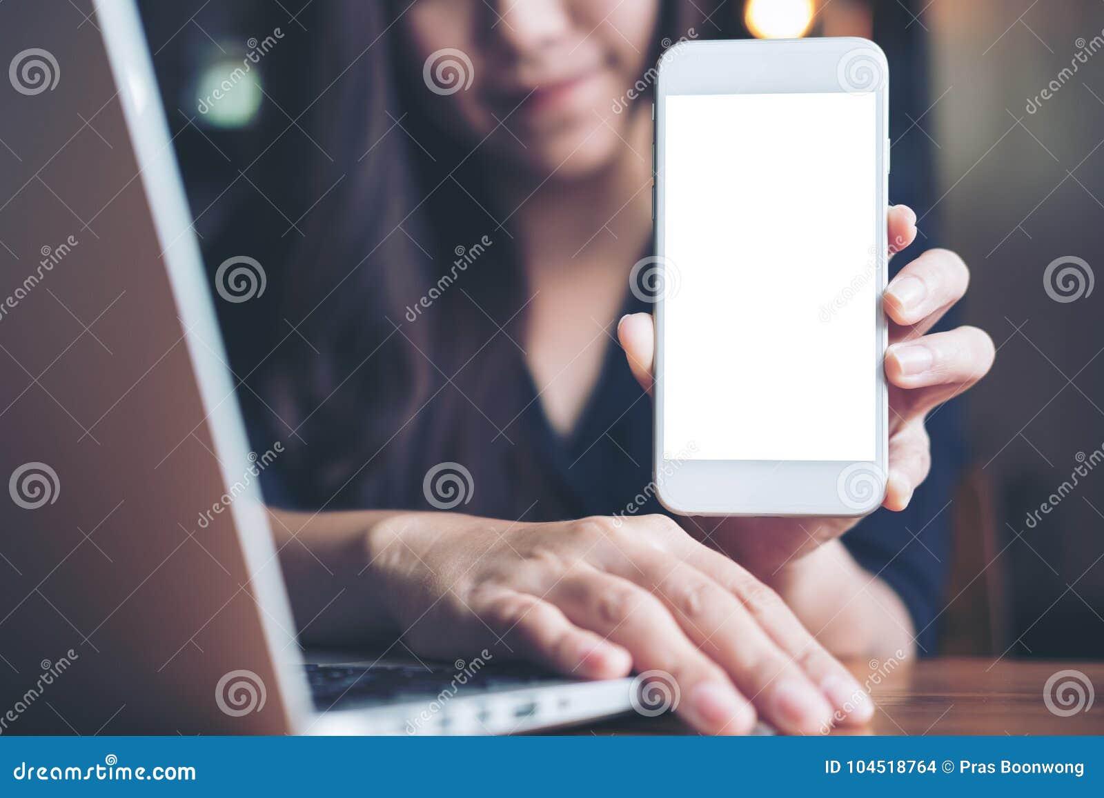 Image de maquette d une belle femme asiatique souriante tenant et montrant le téléphone portable blanc avec l écran noir tout en