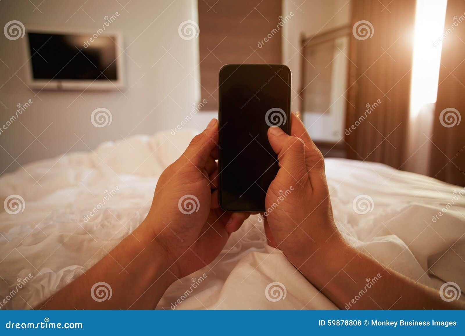 Image de point de vue de téléphone portable de Person In Bed Looking At
