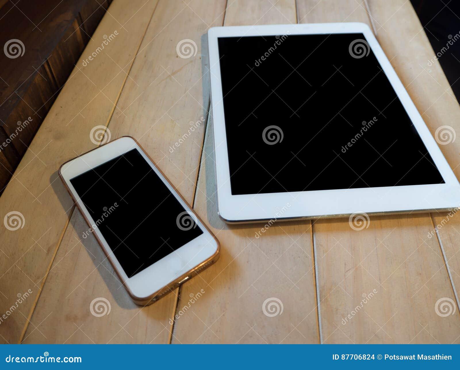 Image de vue supérieure de dispositif de smartphone et de comprimé au-dessus de table en bois