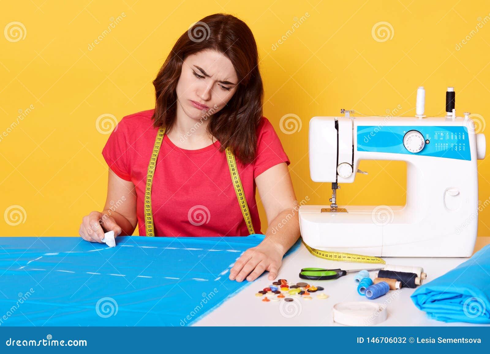 Image du couturier féminin attirant travaillant dans son atelier, étant en cours de créer la nouvelle collection de vêtements, fa