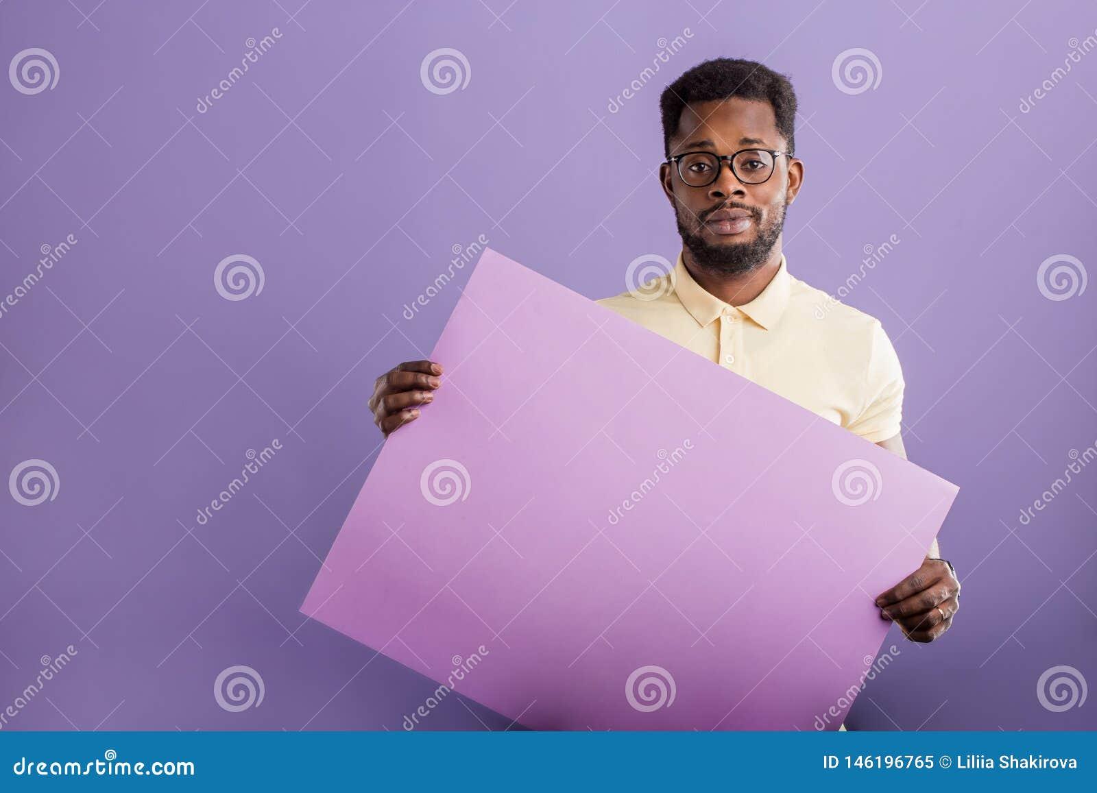 Image du jeune homme d afro-américain tenant le conseil vide sur le fond violet
