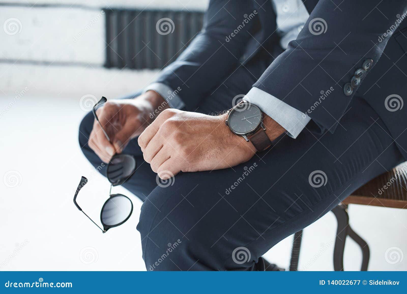 Image en gros plan d un homme d affaires élégant qui s assied sur la chaise avec la montre marquée sur sa main et tient des verre