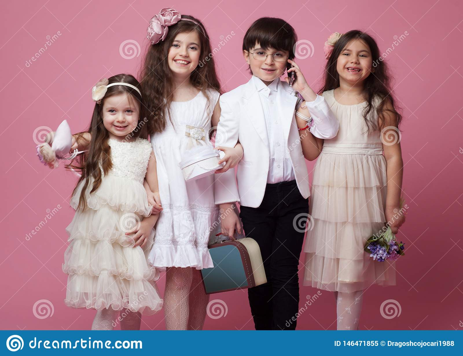 Frontal portrait of a group of happy children dressed in beautiful classic clothing, isolated on pink background.