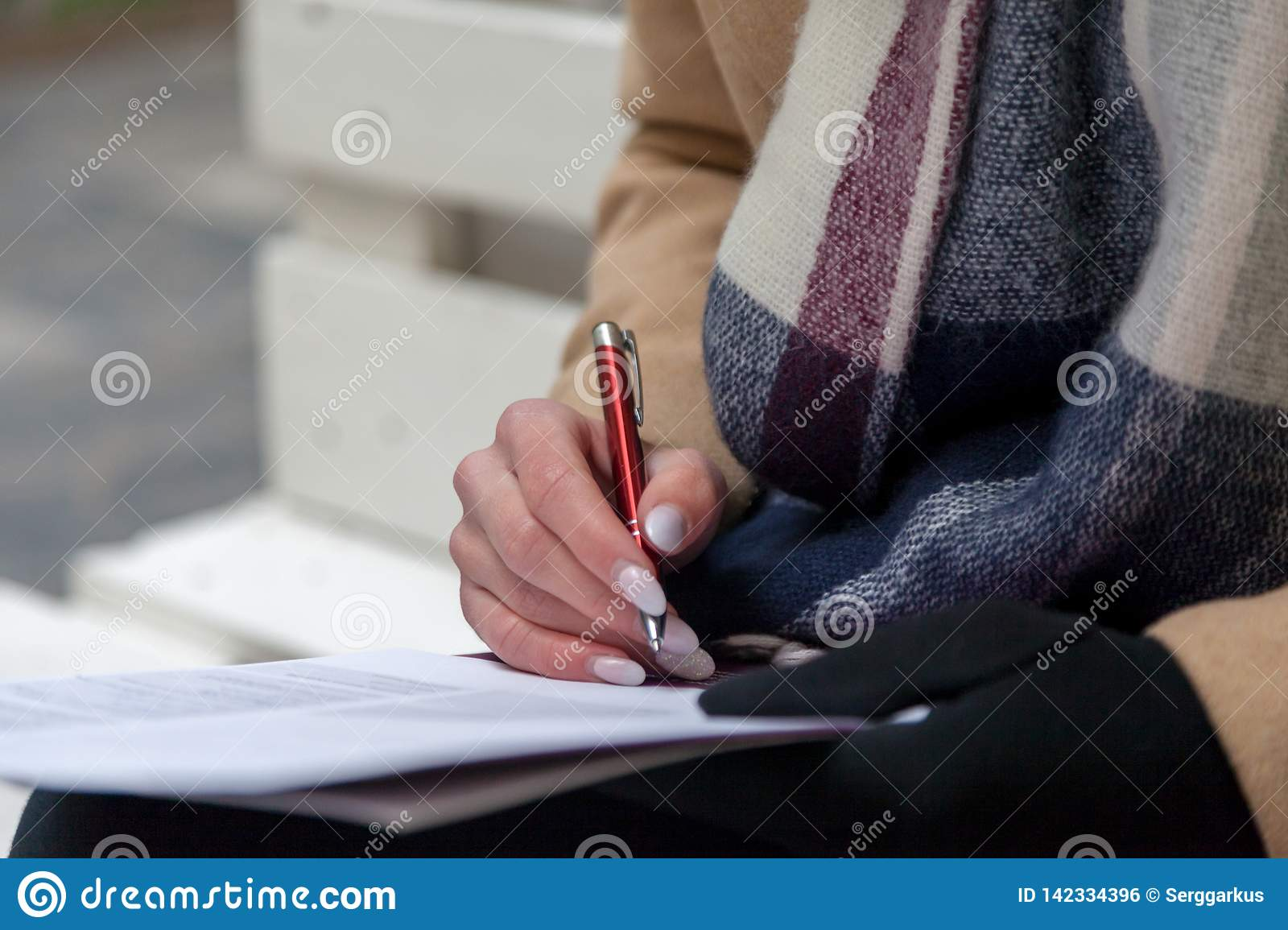 An image of a hand and pen completing a form.