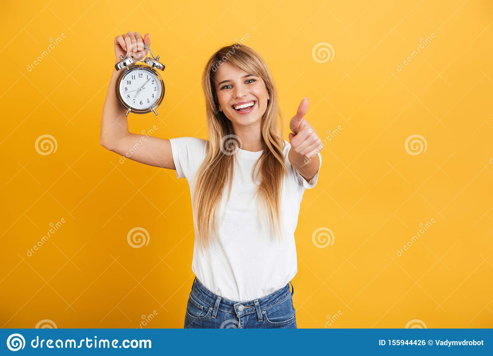 Happy smiling young blonde woman posing isolated over yellow wall background dressed in white casual t-shirt holding alarm clock