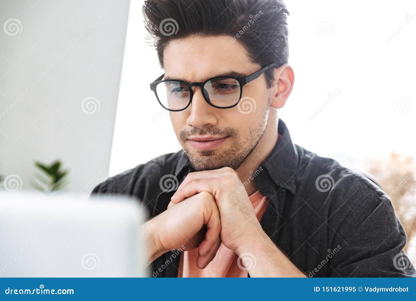 Image haute étroite d homme bel sérieux concentré dans des lunettes