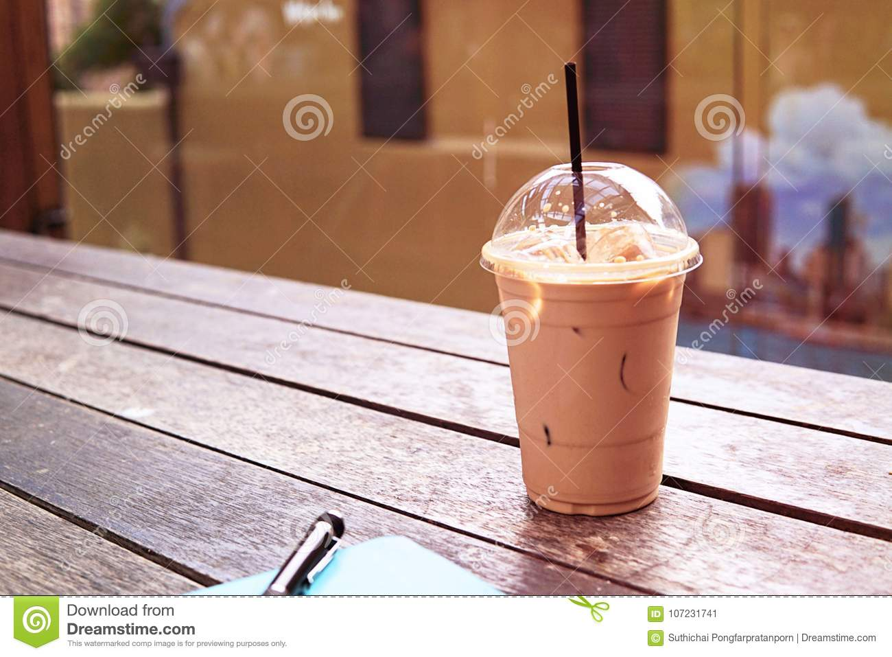 Ice coffee in takeaway cup with notebook and pen on the side. Bo