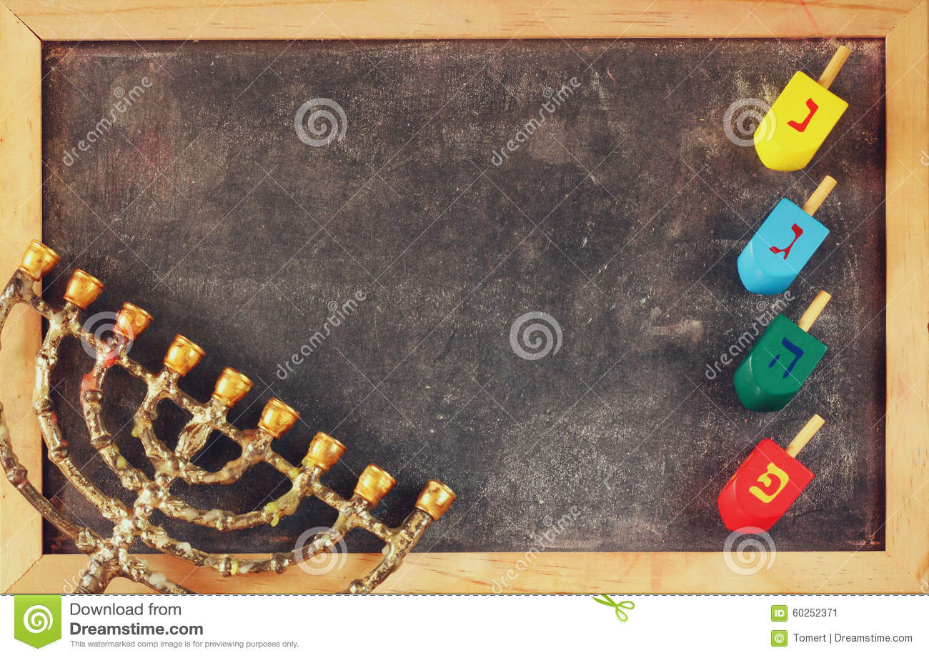 image of jewish holiday Hanukkah with menorah (traditional Candelabra) and wooden colorful dreidels (spinning top) over chalkboard