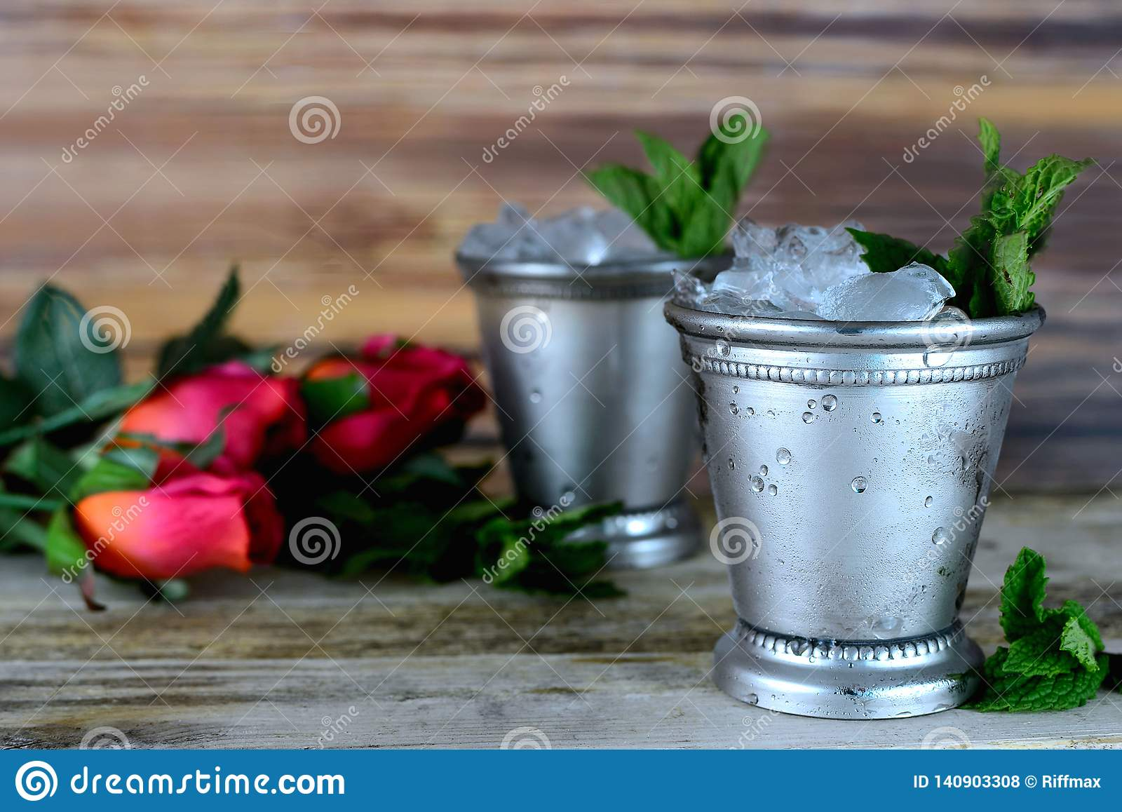 Image for Kentucky Derby in May showing two silver mint julep cups with crushed ice and fresh mint in a rustic setting