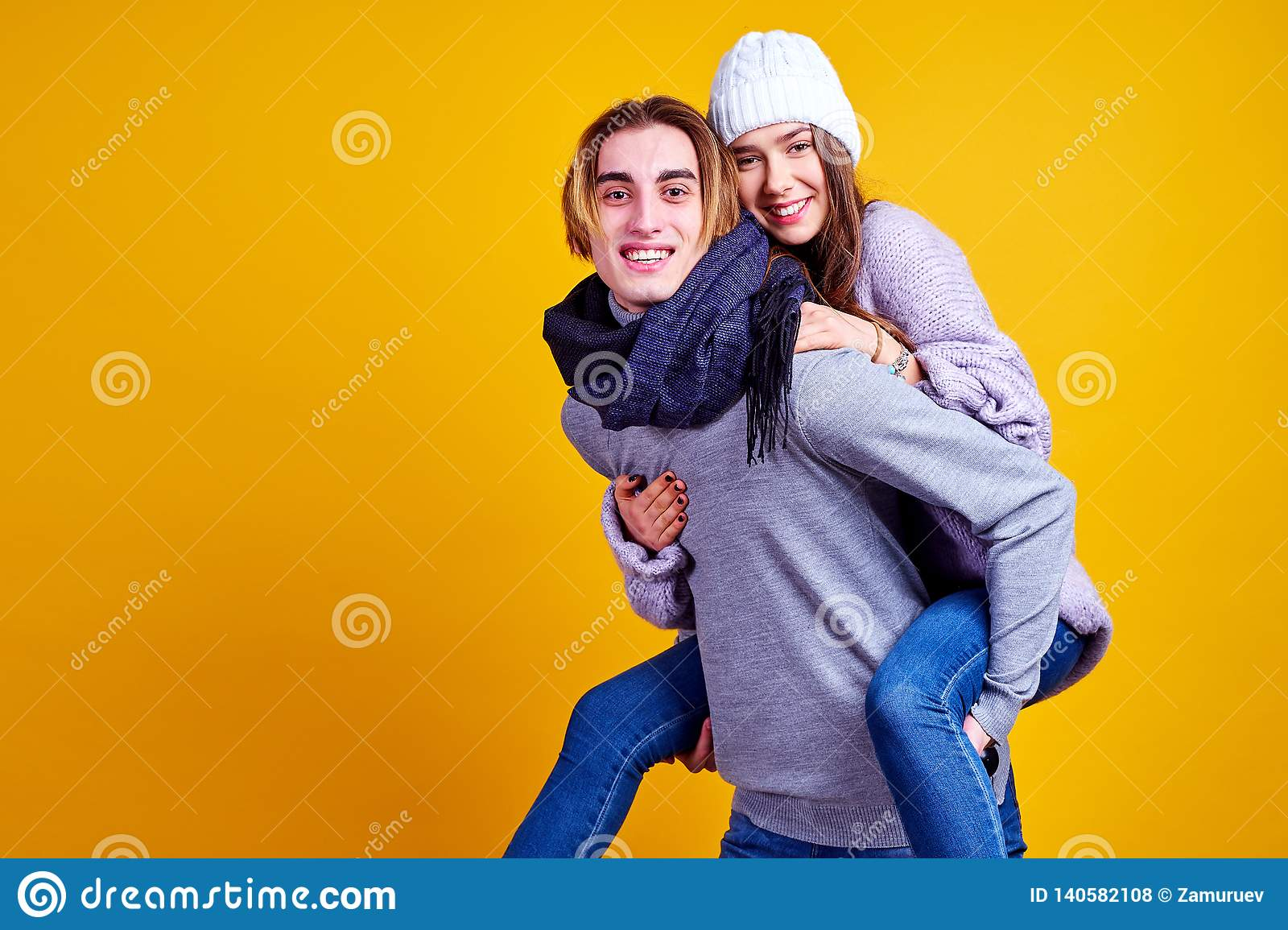 Image of lovely couple having fun while man piggybacking his girlfriend on yellow background