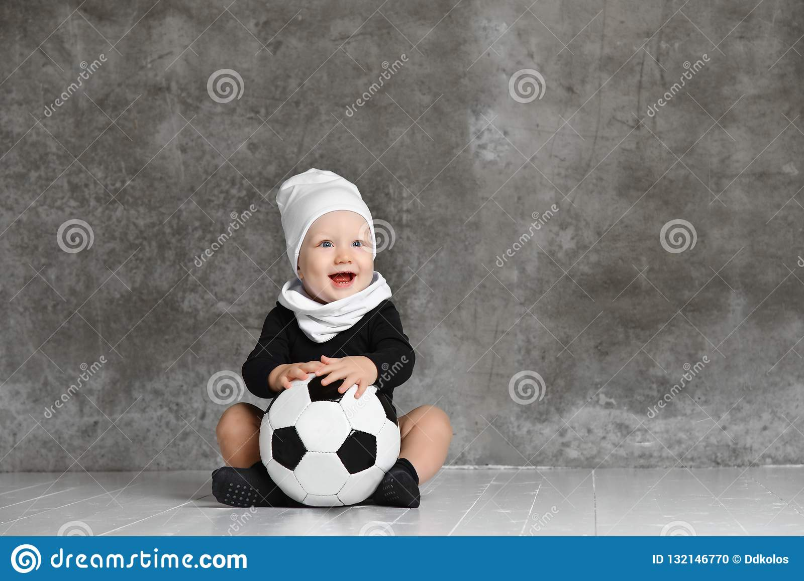Image mignonne de bébé tenant un ballon de football