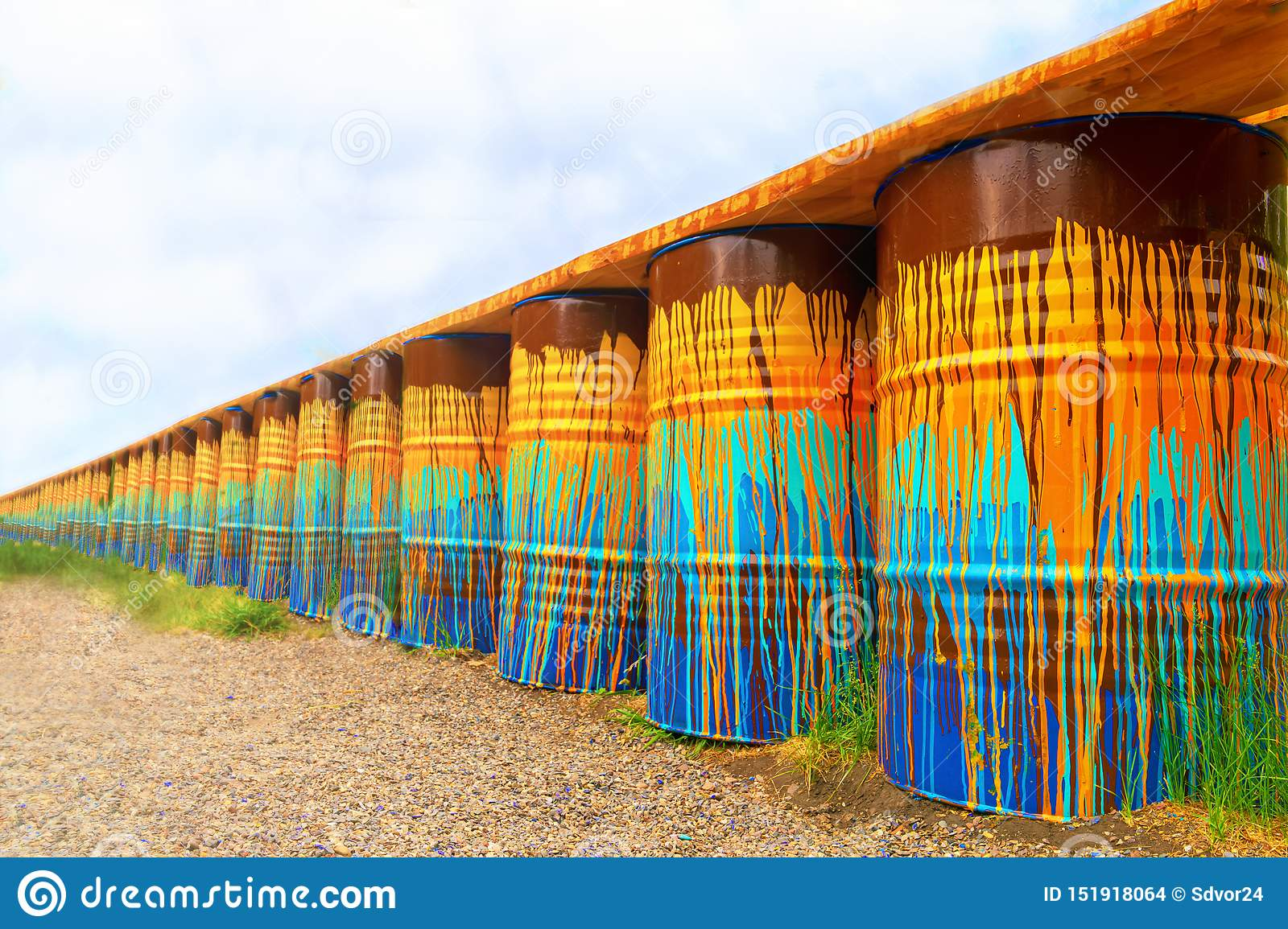 Image of multi-colored, rusty and old oil barrels in piles with a blue sky and sunny day. barrels perspective, like a