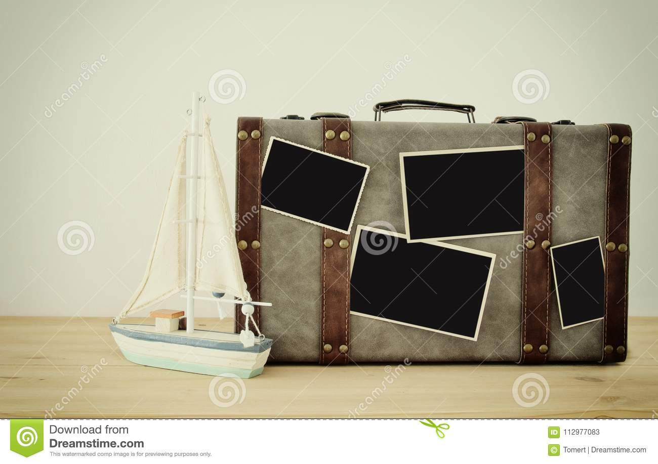 Image of old vintage luggage, vintage boat and blank photos for photography montage mockup over wooden floor.
