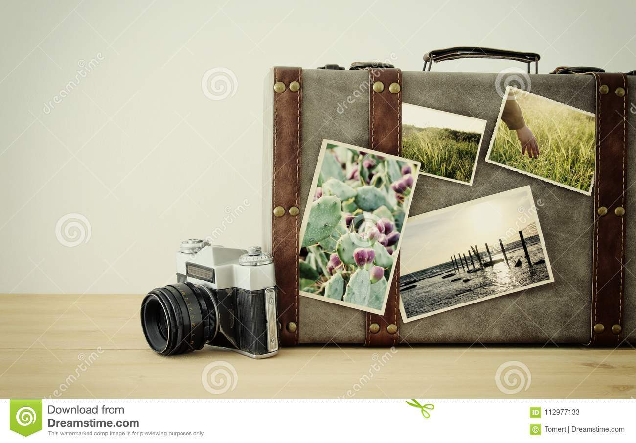 Image of old vintage luggage, fedora hat and vintage old photo camera with nature photos over wooden floor.