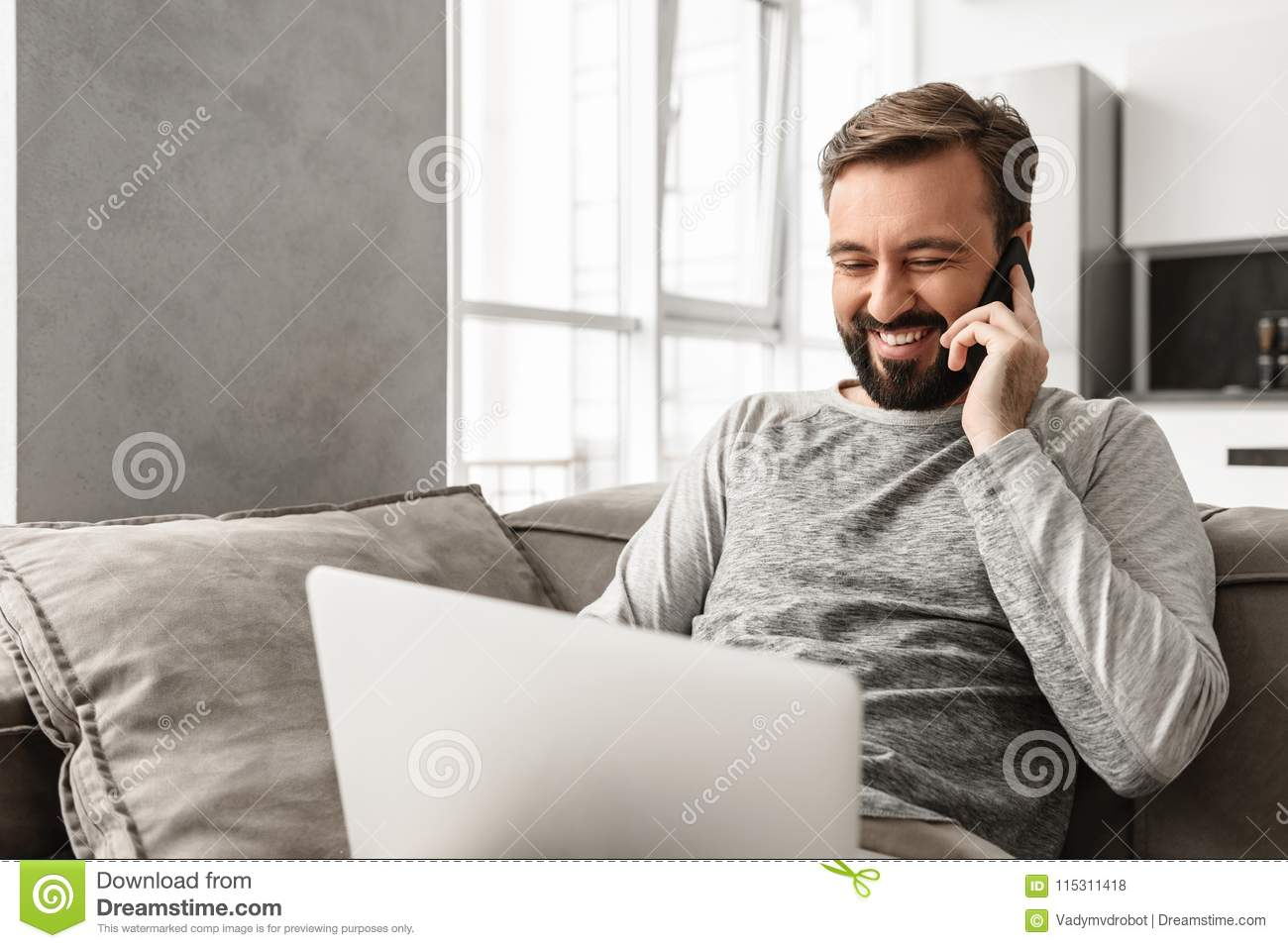 Image of positive man 30s in casual wear sitting on sofa in living room, while using laptop and speaking on cell phone