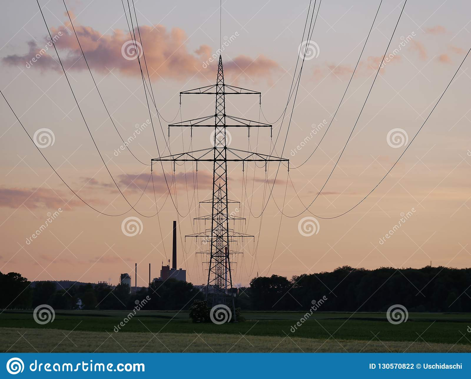 Image of power line during sunset with power plant