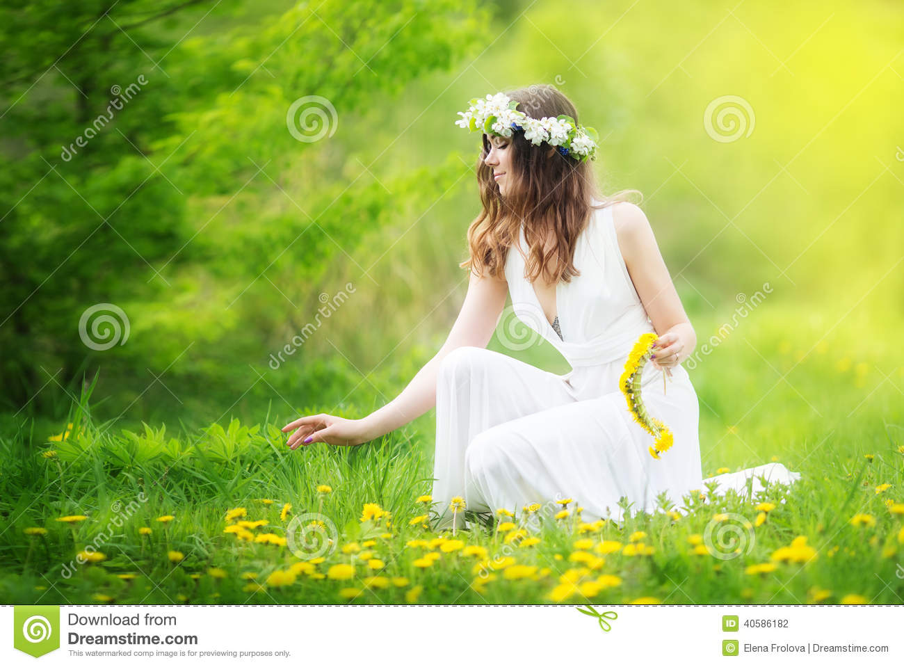 Image of pretty woman in a white dress weaves garland from dandelions in the field, happy cheerful girl resting on dandelions me