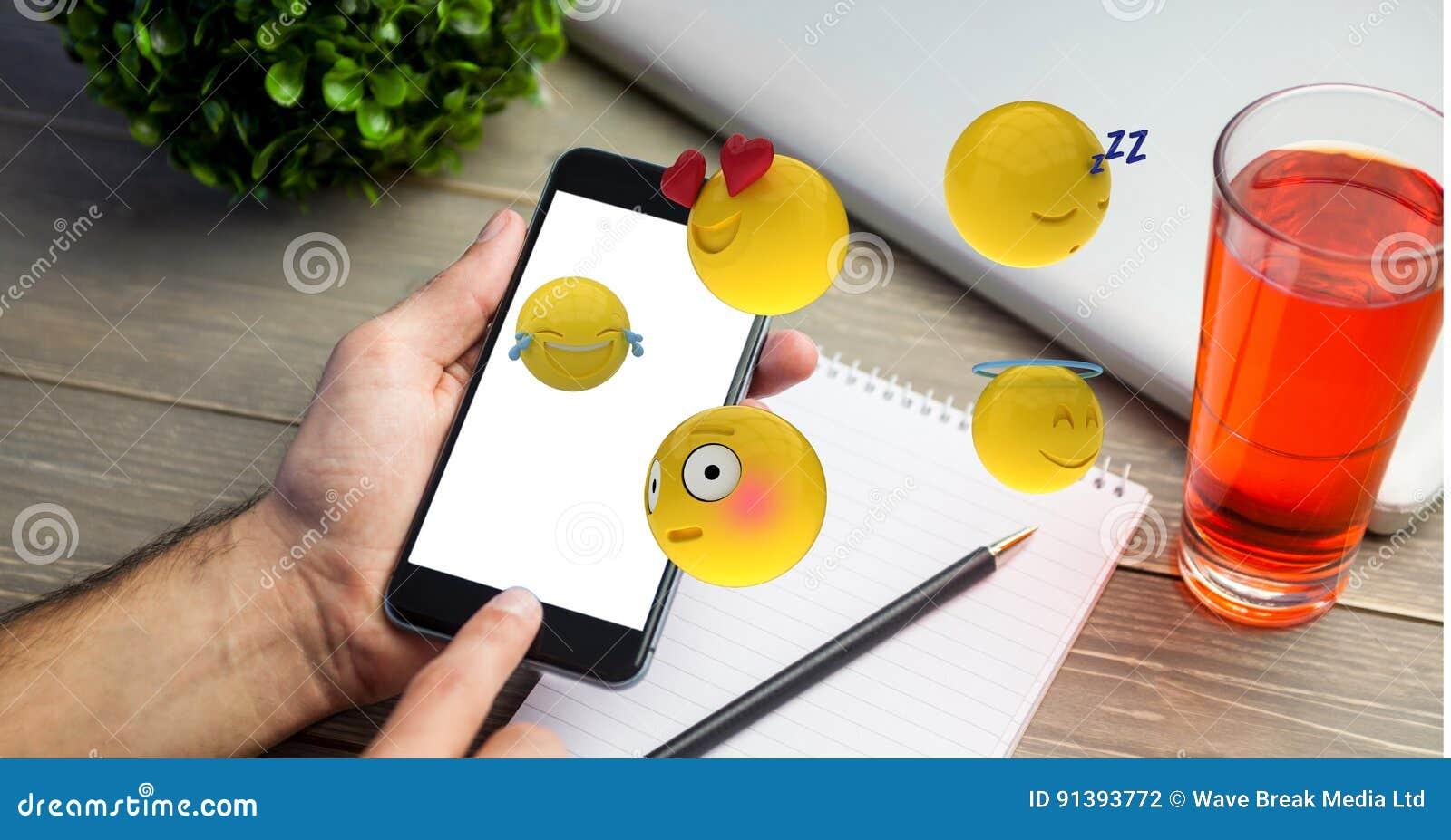 Image produite par Digital des emojis volant au-dessus de la main utilisant le téléphone intelligent par la boisson sur la table