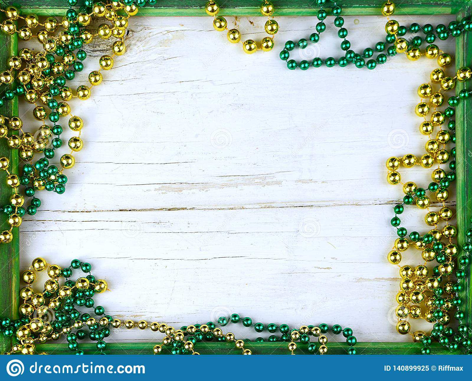 Image for Saint Patrick`s Day on March 17th. Shiny green and gold beads on a wooden frame with rustic woden background.
