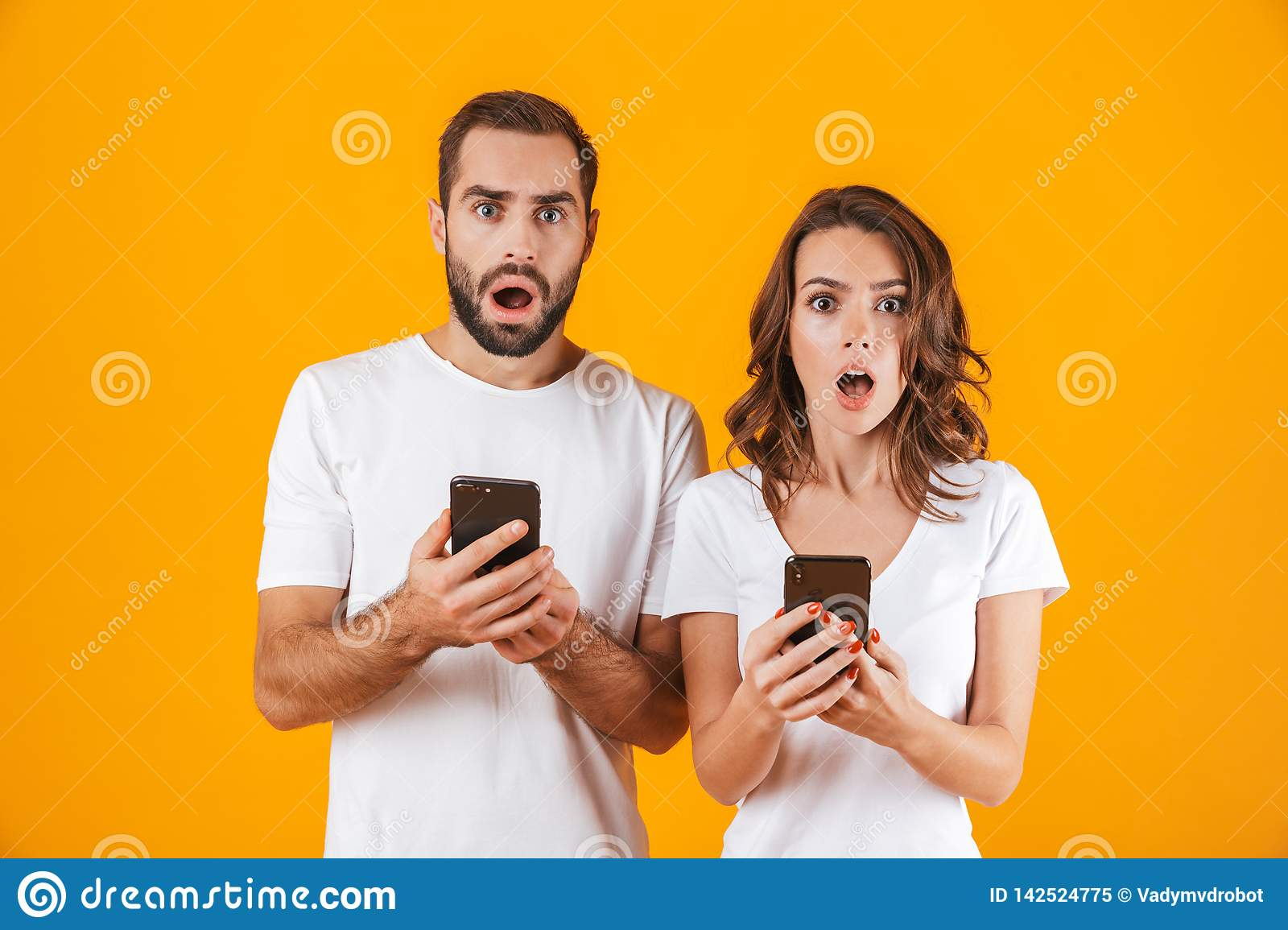 Image of shocked couple man and woman using smartphones together, isolated over yellow background