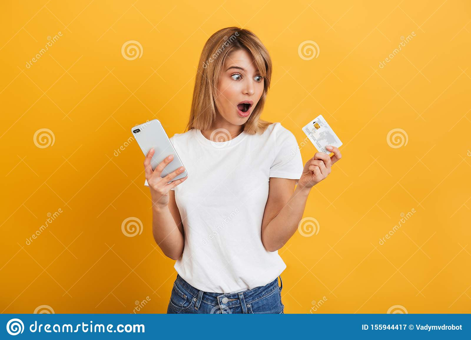 Shocked surprised young blonde woman posing isolated over yellow wall background dressed in white casual t-shirt using mobile
