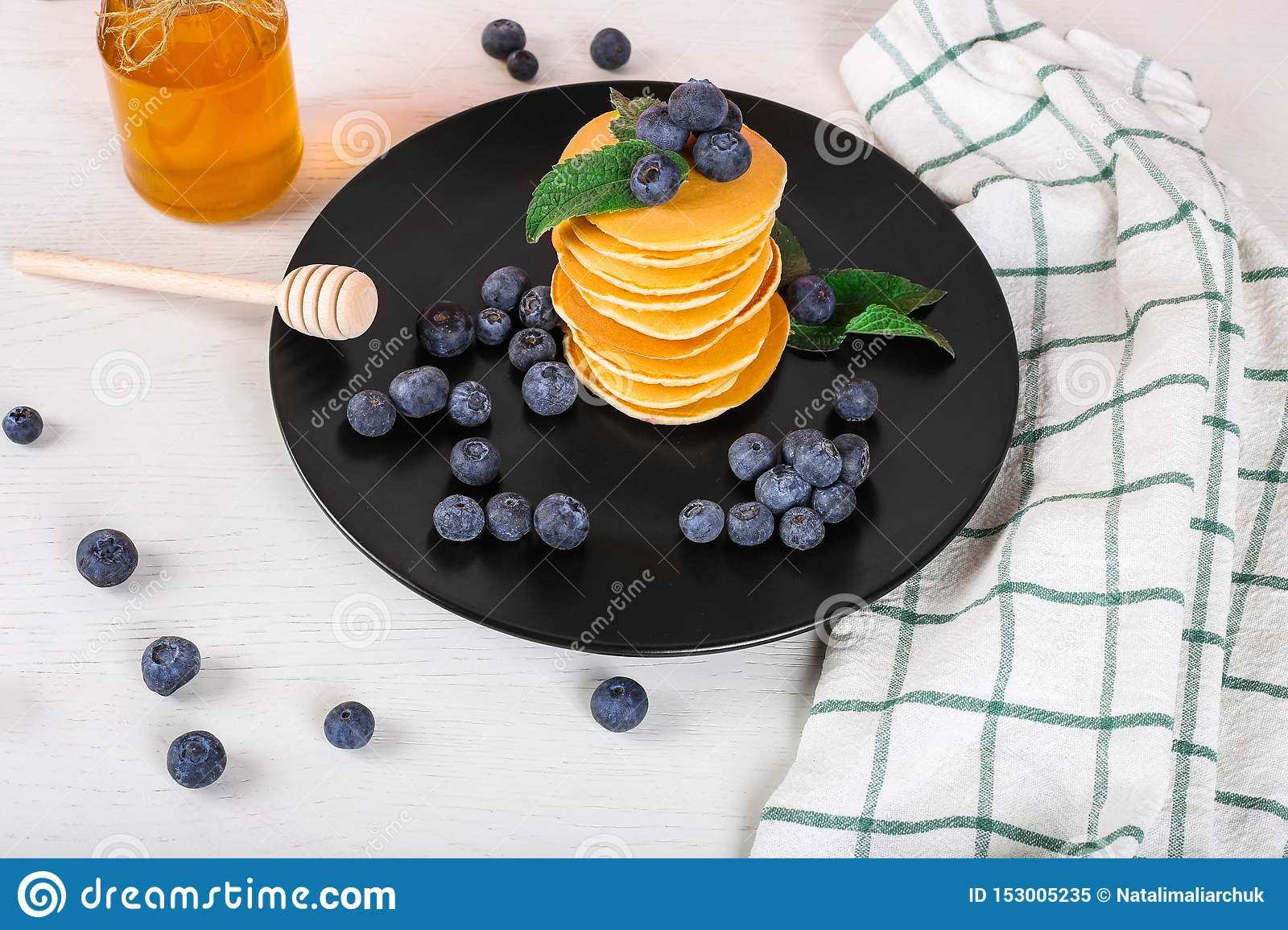 Image shows a homemade fluffy pancake with blueberry and mint on the top; situation is decorated with white wooden table and honey