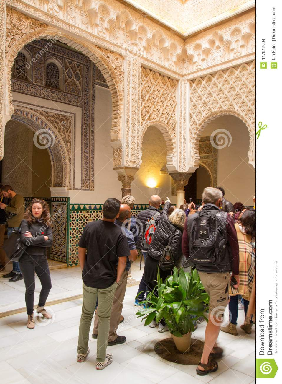tourist viewing the islamic architecture of the alcazar in seville