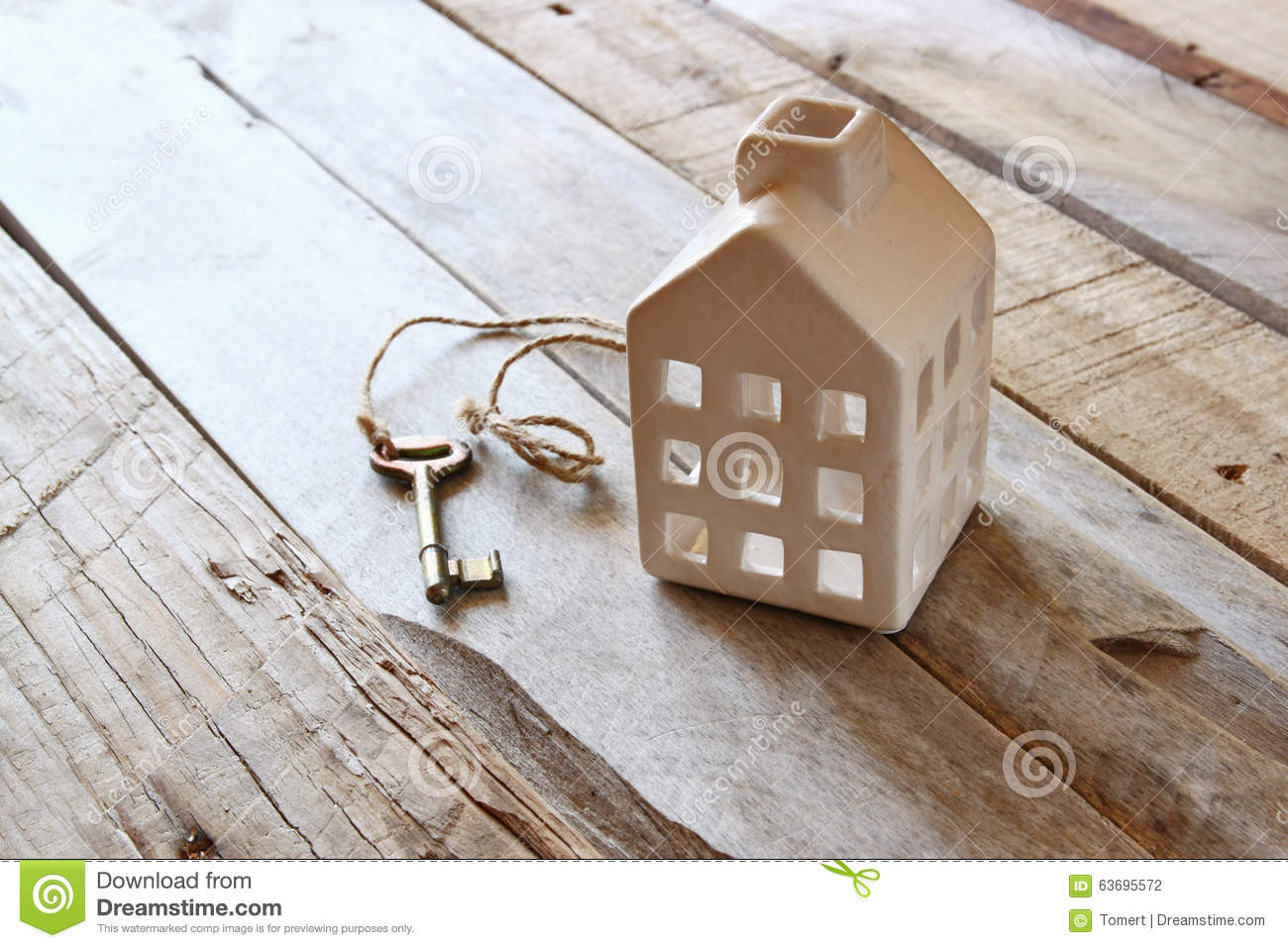 Image of small miniature house and old key over rustic wooden table.
