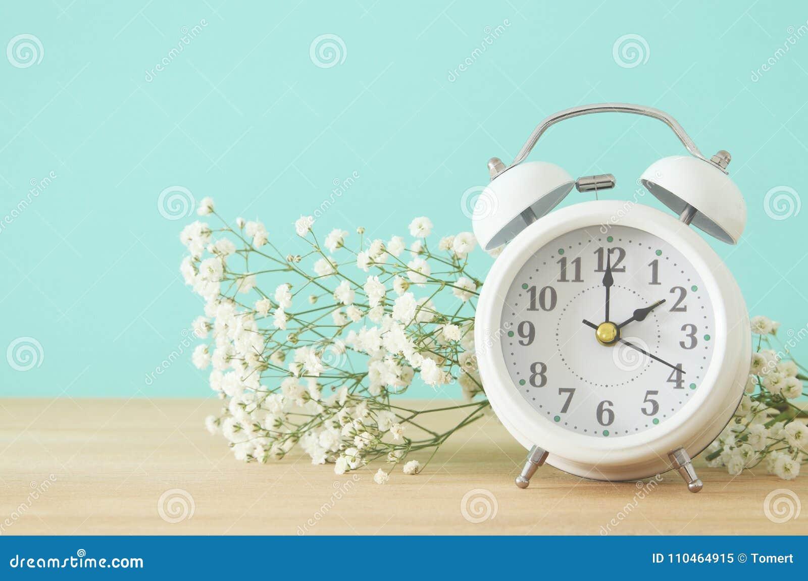 Image of spring Time Change. Summer back concept. Vintage alarm Clock over wooden table.