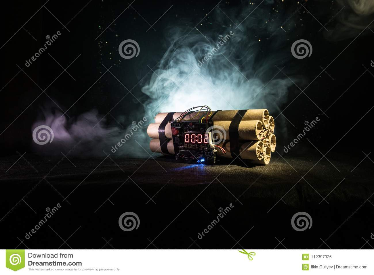 Image of a time bomb against dark background. Timer counting down to detonation illuminated in a shaft light shining through the d