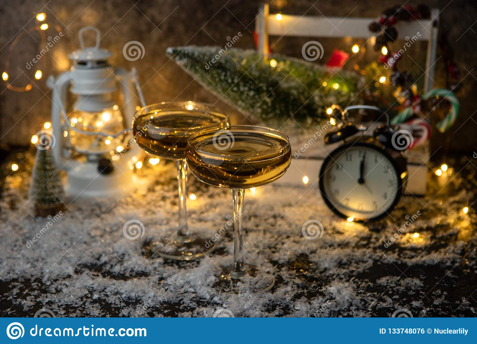 Image of two champagne glasses on blurred background with Christmas tree, lantern, clock