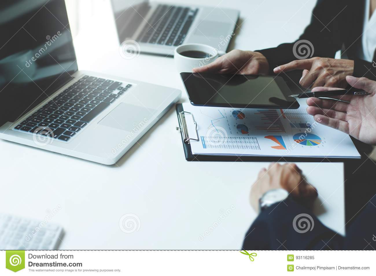 Image of two young business executives using touchpad at meeting