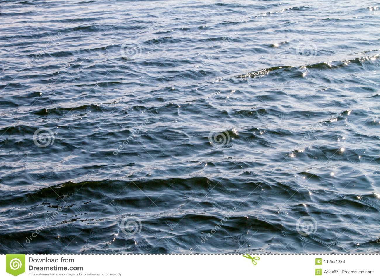Water surface of the river with waves and sunlight reflections