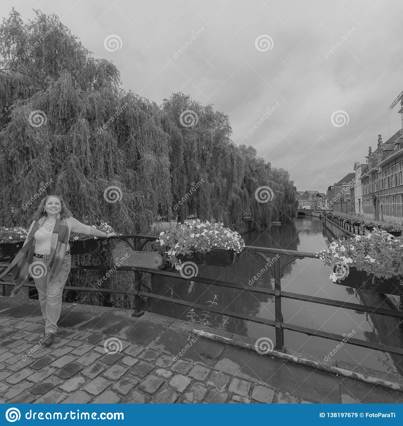 Image of a woman leaning on a metal fence on a bridge with a canal in the background