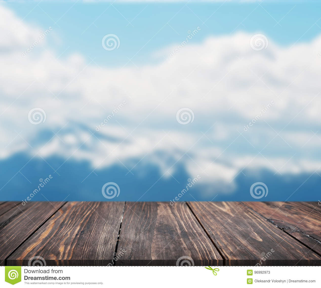 Image of wooden table in front of abstract blurred background of mountain. can be used for display or montage your products. Mock