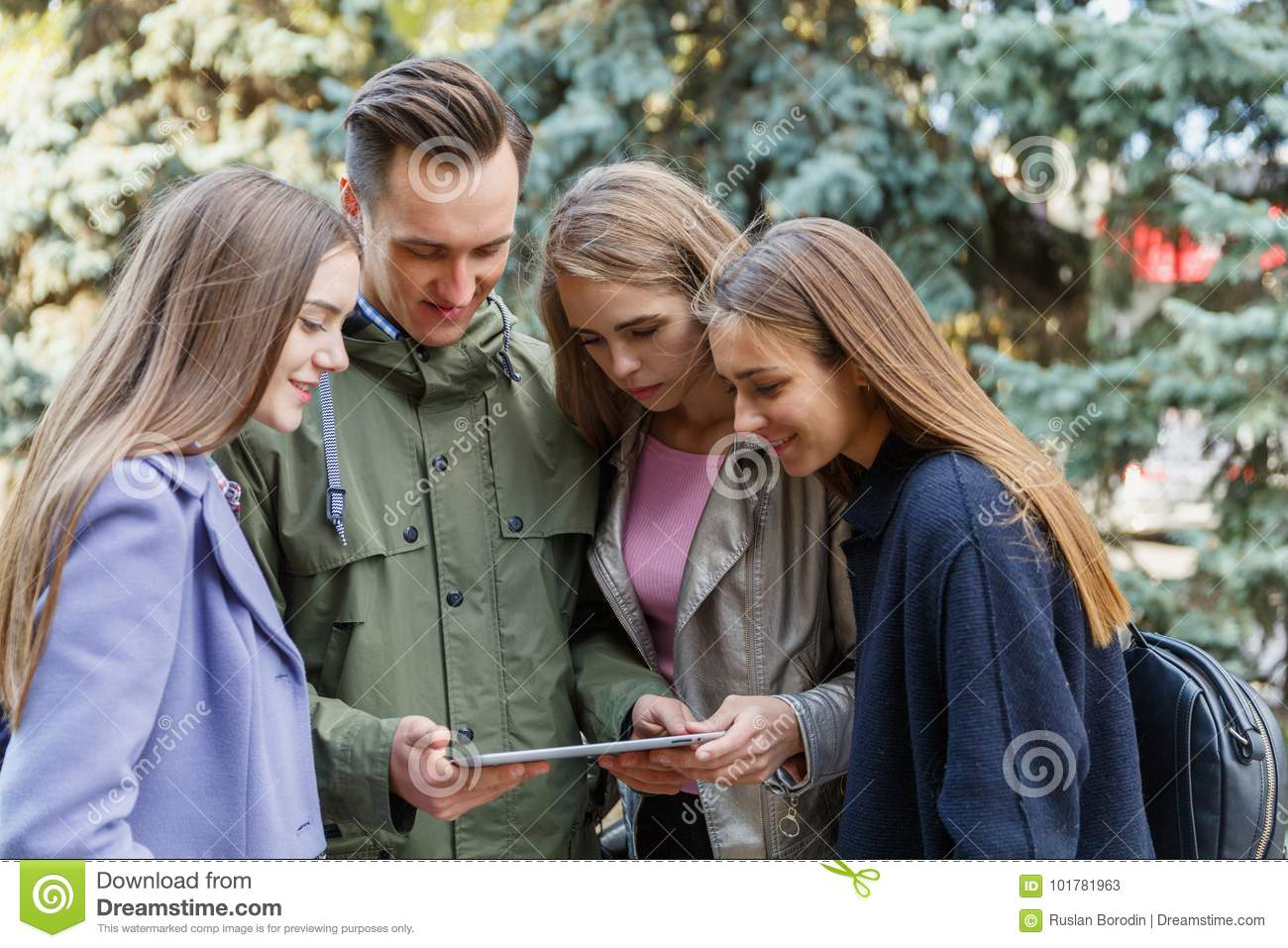 Image of young friends outdoors with a computer in hands of a young man.