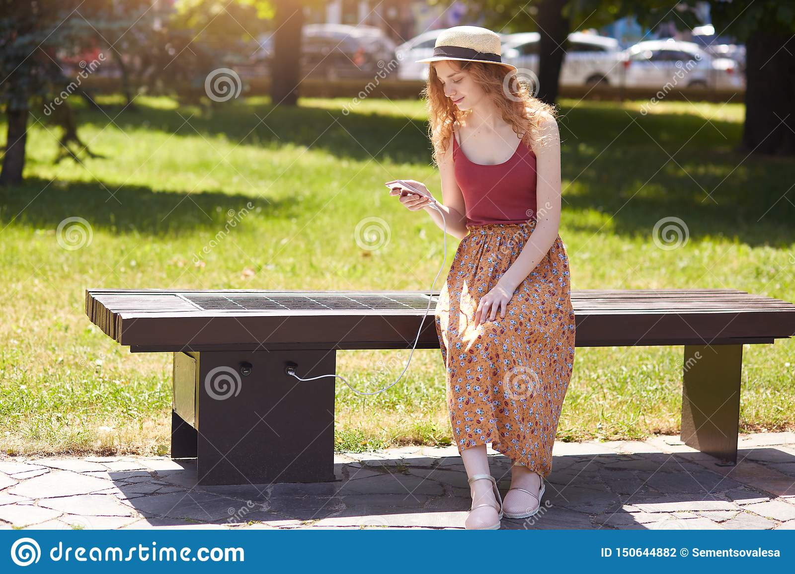 Image Of Young Girl Charges Mobile Phone Via USB Outdoors