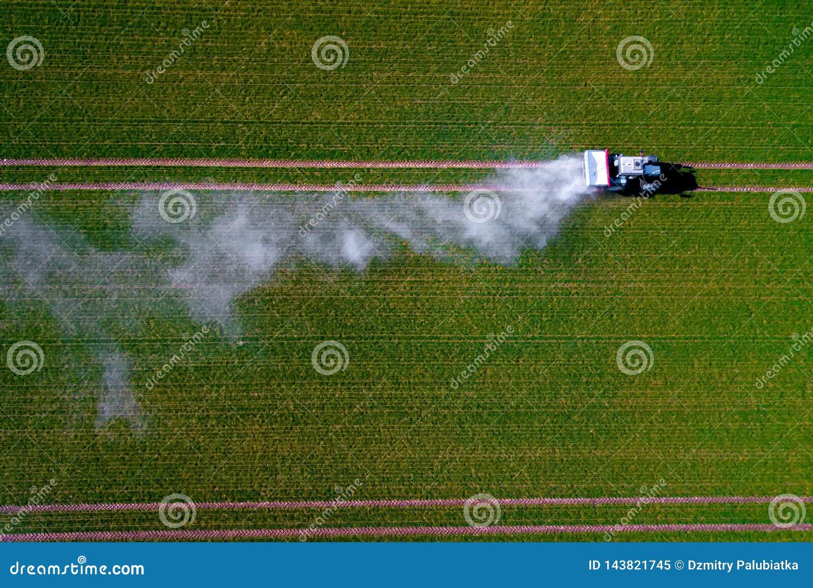 Imagem aérea de inseticidas de pulverização do trator no tiro verde do campo da aveia do zangão