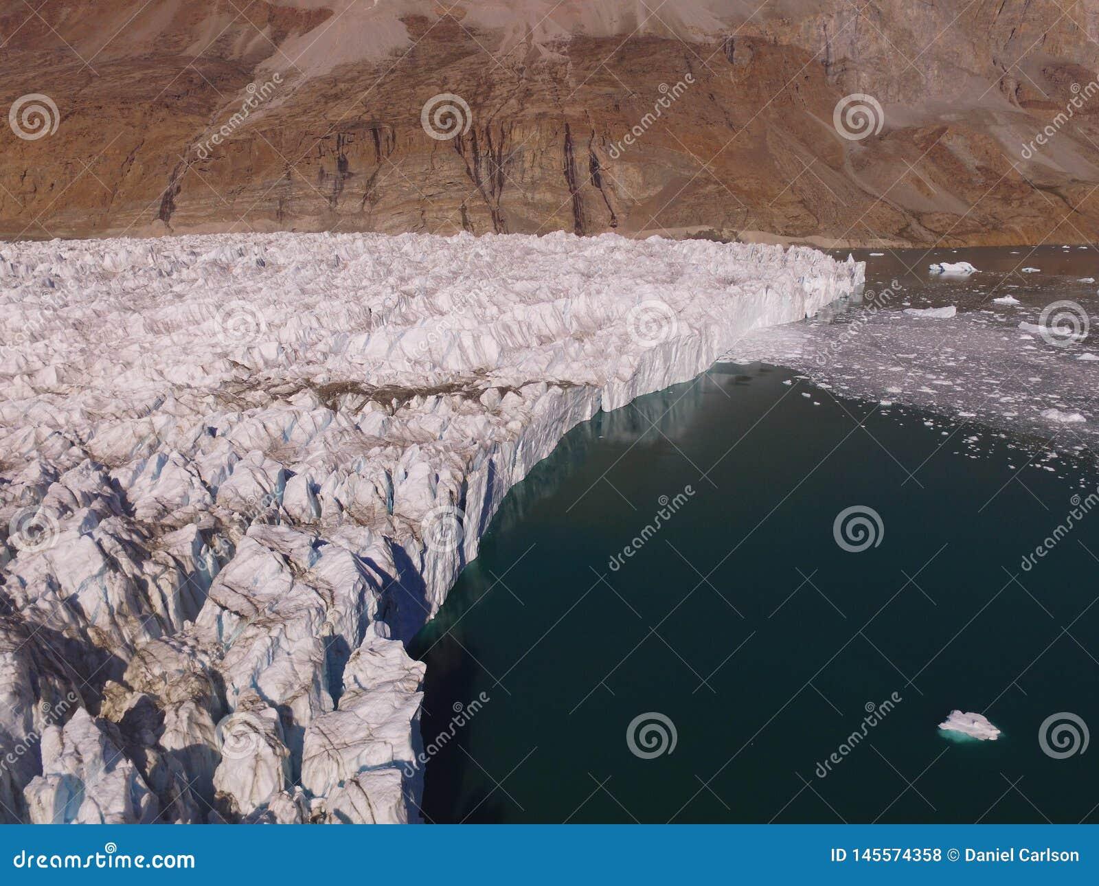 Imagem aérea do zangão oblíquo do término de uma geleira em um fiorde em Gronelândia do nordeste