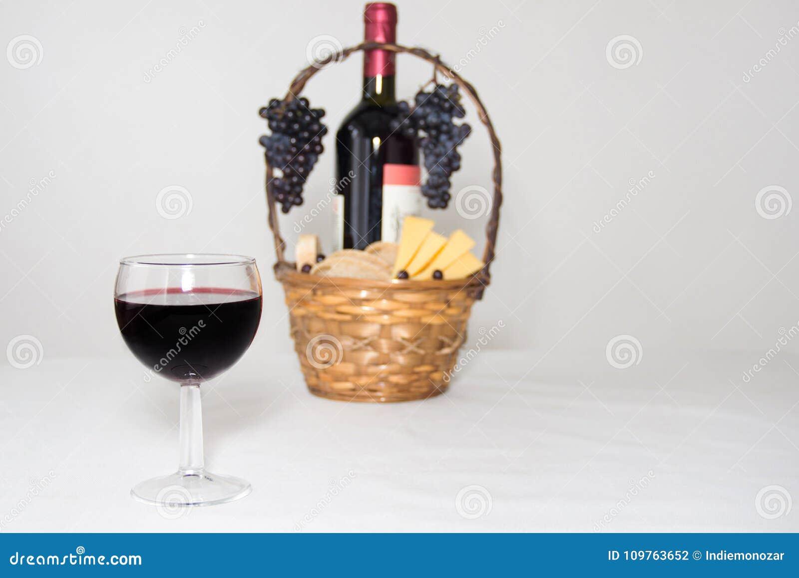 Imagem abstrata de um vidro do vinho Uma garrafa do vinho tinto, das uvas e da cesta do piquenique com fatias do queijo no fundo