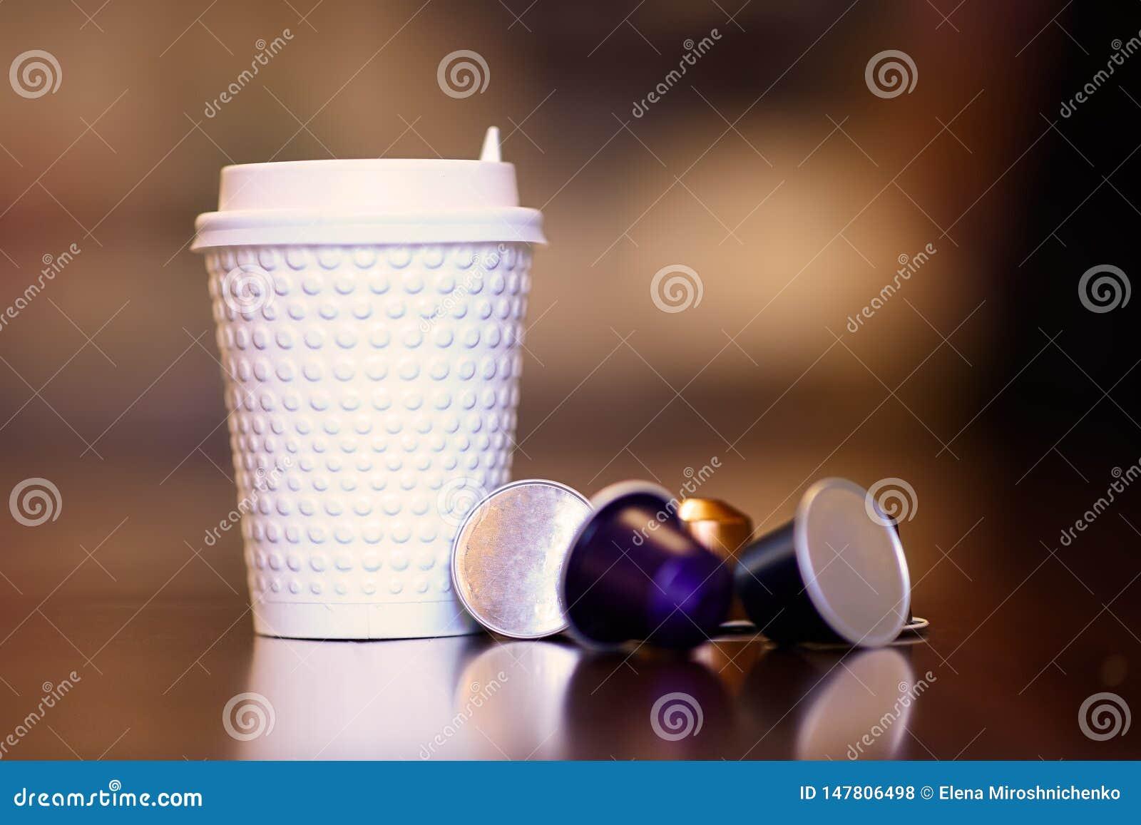 Imagem ascendente próxima do copo plástico branco do coffe com alguns cartuchos substituíveis coloridos com café