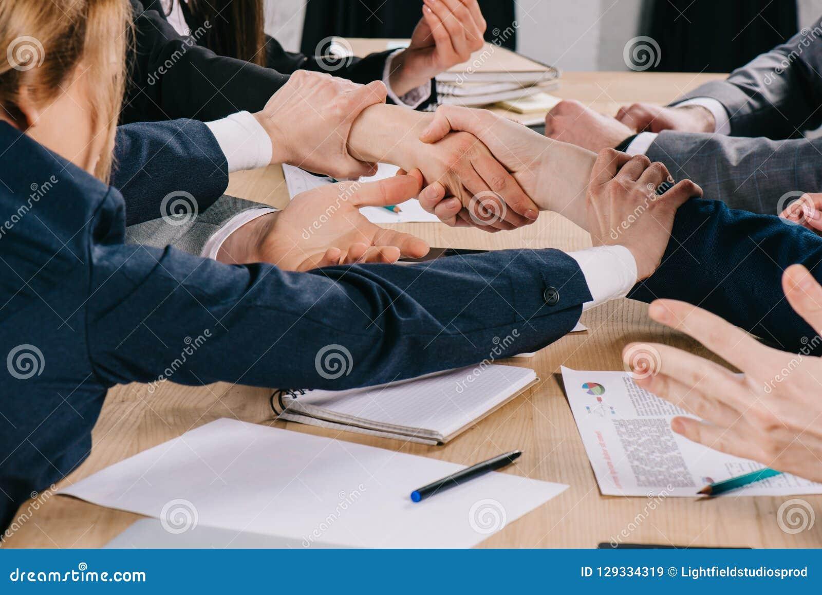 Imagem colhida de dois sócios comerciais que agitam as mãos quando mulher de negócios