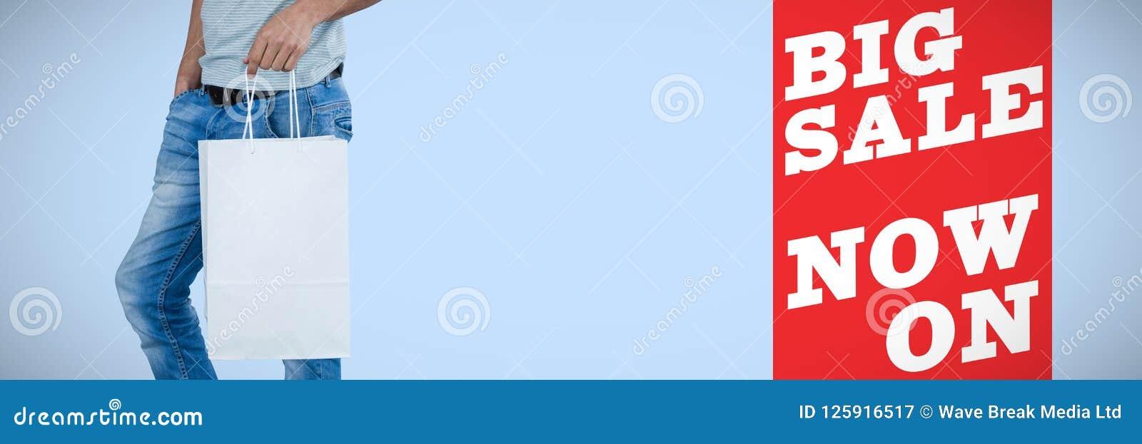 Imagem composta da baixa seção do homem que mantém o saco de compras contra o fundo branco